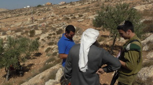 DCO officers tries to prevent Palestinians from picking olives near Avigayil Israeli illegal outpost.