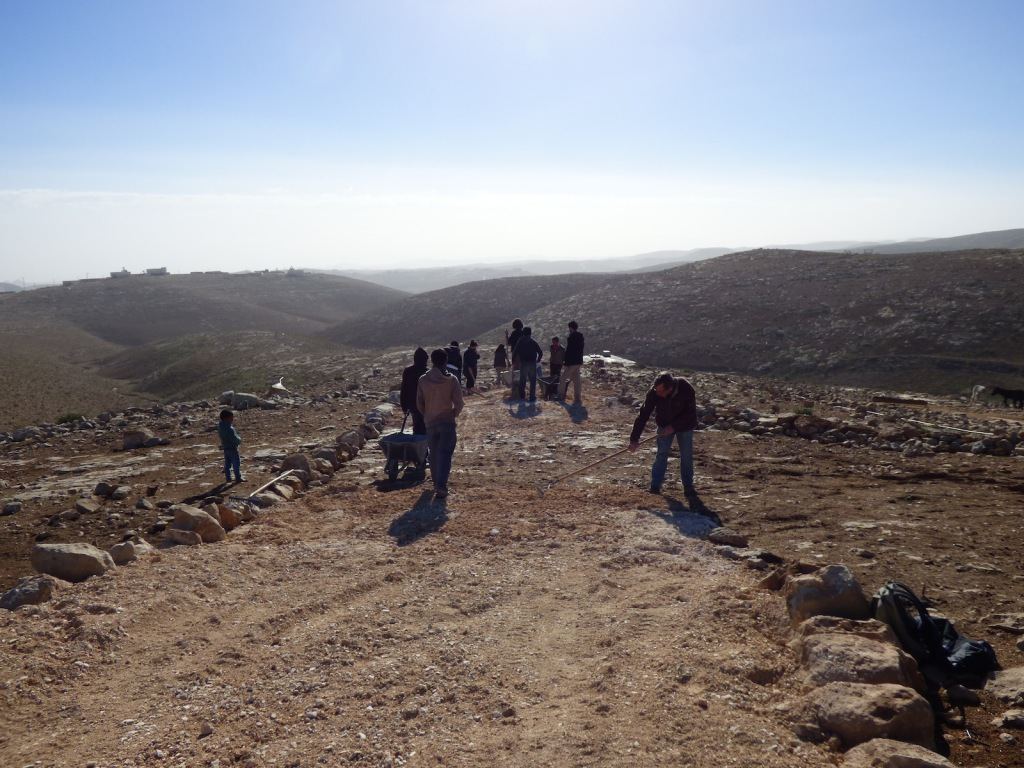 Palestinians and Israeli activists work at the new dirt-patch on December 13.