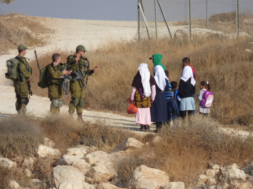 Schoolchildren at the meeting point with the Israeli military escort, between Havat Ma'on illegal outpost and Ma'on settlement.