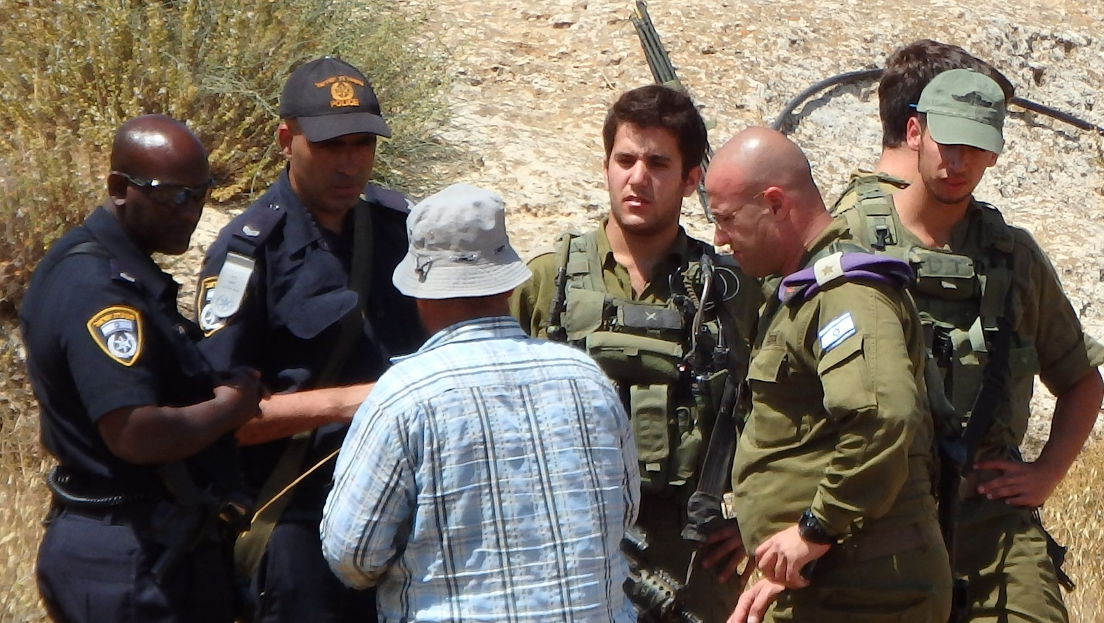 The Palestinian owner of the uprooted trees speaking with Israeli Police, DCO and Army officers