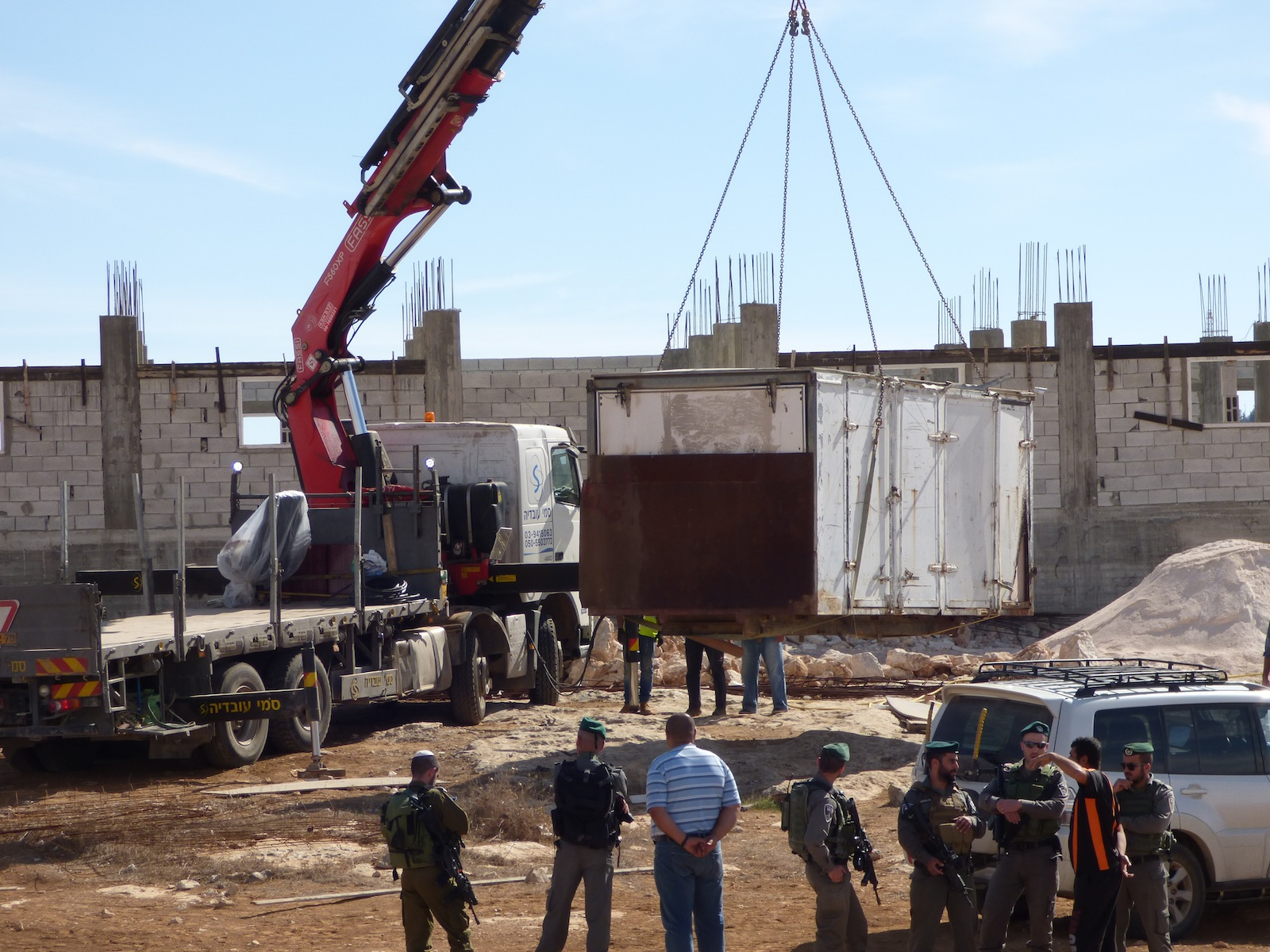 Israeli forces confiscate a container full of building materials