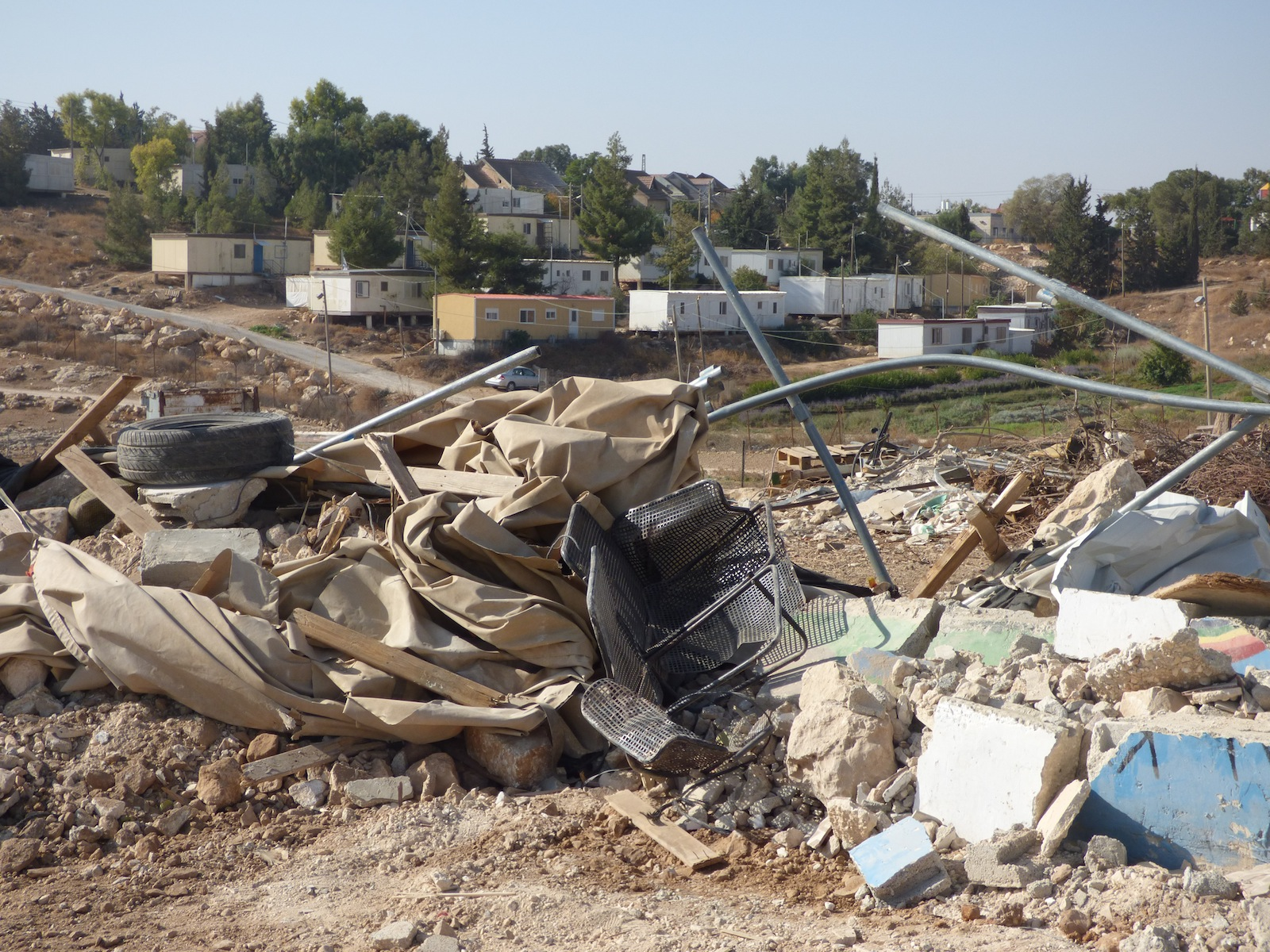 Umm Al-Kheir community center demolished for the second time,  in the background Carmel Israeli settlement