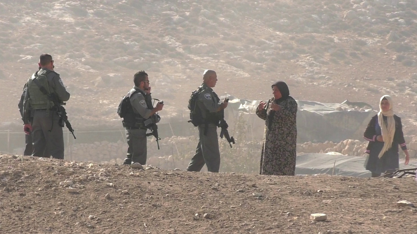 Palestinian woman asks the reason of the raid to Israeli Border policemen