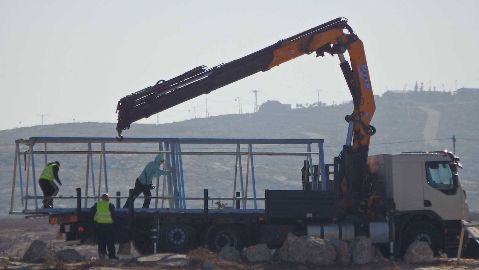 Israeli forces seize Palestinian solar panel system, in the background Mitzpe Yair Israeli illegal outpost