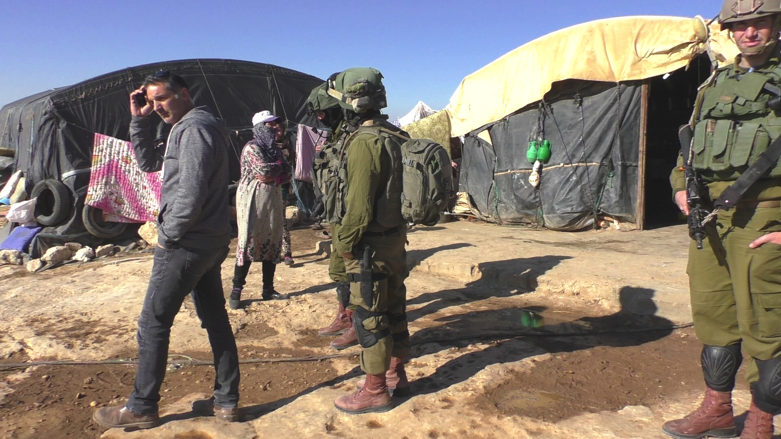 Israeli soldiers escort DCO officer in Susya Palestinian village